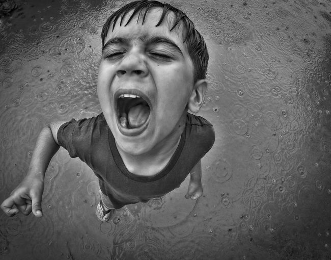 Overhead View Of A Child With Mouth Open In The Rain