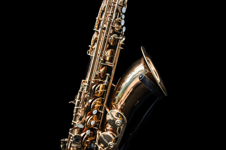 A golden saxophone. Foot STAND Sax Standing Arts Culture And Entertainment Black Background Brass Brass Instrument  Close-up Cut Out Gold Colored Metal Music Musical Instrument No People Saxophone Single Object Studio Shot