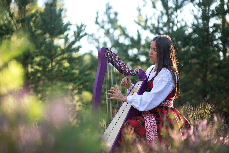 Woman playing harp against trees in forest