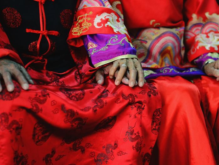 Midsection Of Senior Couple Sitting In Red Traditional Clothing