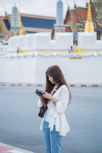 Young woman using mobile phone standing by road