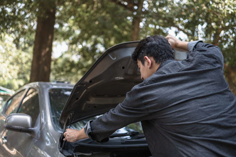 Rear view of man repairing car outdoors