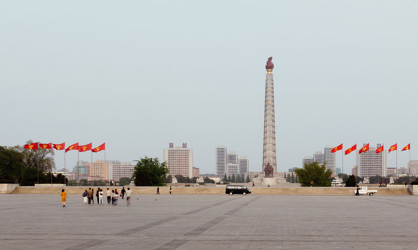 North Korea Architecture Building Building Exterior Built Structure City Clear Sky Day Flag Incidental People Juche Tower Nature Office Building Exterior Outdoors Patriotism Pyongyang Sky Skyscraper Street Tall - High Tourism Tower Travel Travel Destinations