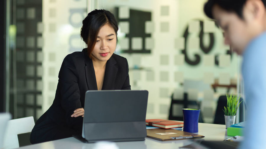 Young businesswoman looking at digital tablet in office
