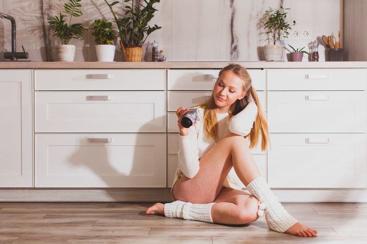 Portrait of smiling girl sitting on wooden floor at home