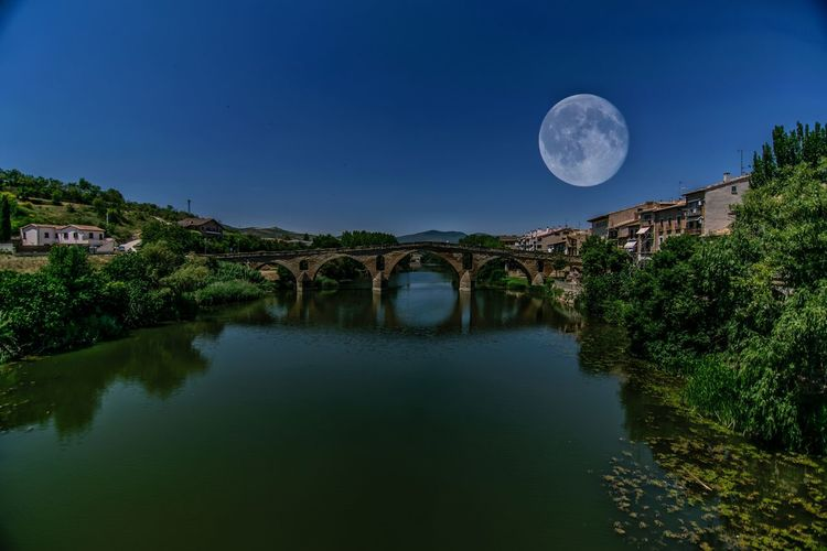 Scenic View Of Moon Over River Against Sky At Night
