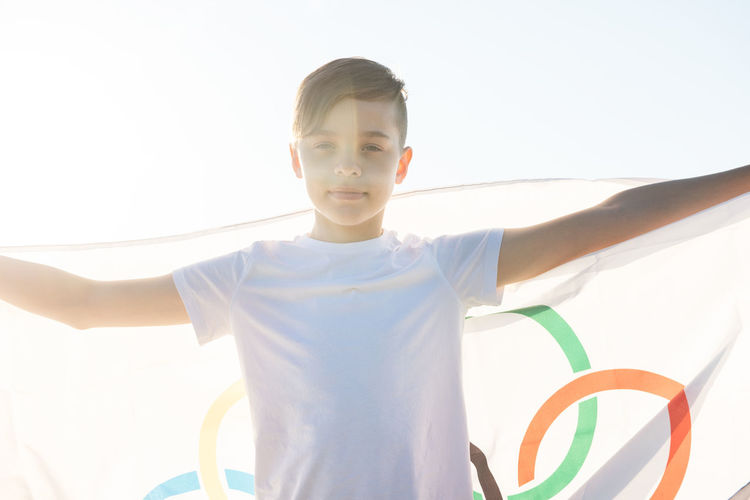 Portrait of boy holding flag while standing outdoors