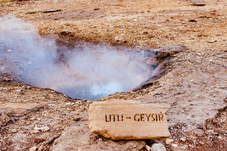 Close-Up Of Text On Rock By Geyser Against Sky