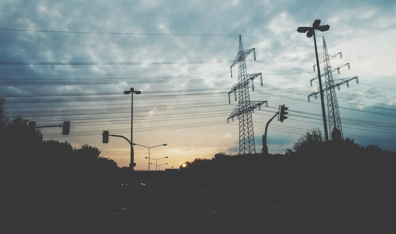 ELECTRICITY PYLONS ON ROAD AGAINST CLOUDY SKY