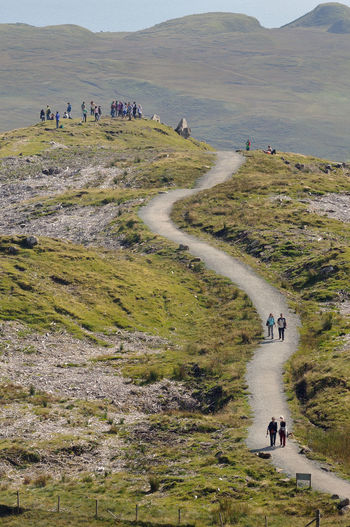 Walkers on the path up to the Old Man of Storr, Isle of Skye Climbing Highlands Landscape Leisure Activity Mountain Mountain Range Non Urban Scene Non-urban Scene Old Man Of Storr Outdoors Path Pathway Remote Rural Scene Scotland Sky Tourism Tranquil Scene Travel Destinations Walking