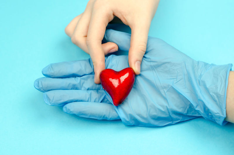 Midsection of man holding heart shape against blue background