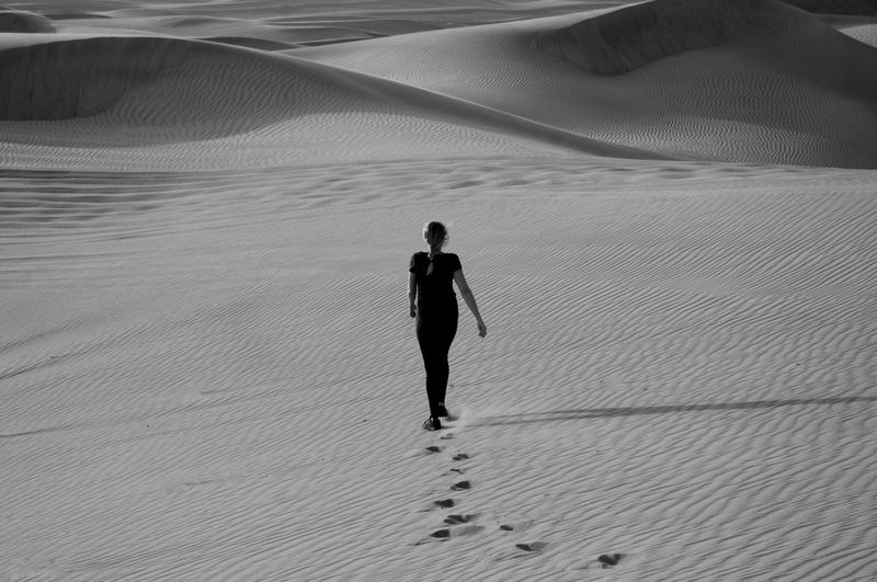 Rear view of mature woman walking on sand dune in desert
