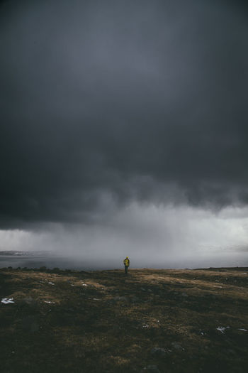 Man Standing On Field Against Storm Clouds