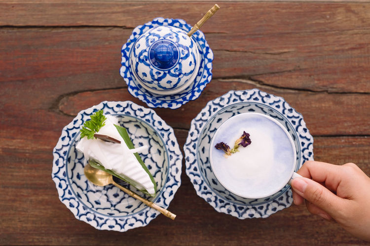 Top view image of a hand holding a cup of hot milk with a piece of cake in an antique Thai traditional benjarong style containers Laying Flat Above View Top Ancient Antique Art Asian  Background Bakery Beautiful Benjarong Blue Cafe Cake Ceramic Classic Clay Closeup Coffee Cup Decor Decoration Delicious Design Dessert Dish Drink Food Hand Kitchenware Luxury Milk Mug Old Pattern Plate Restaurant Retro