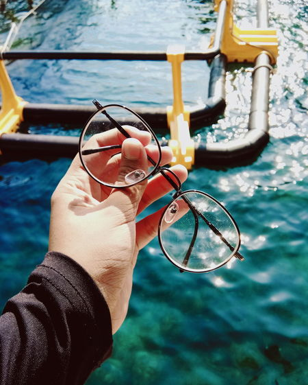 Close-up of hand holding eyeglasses by swimming pool