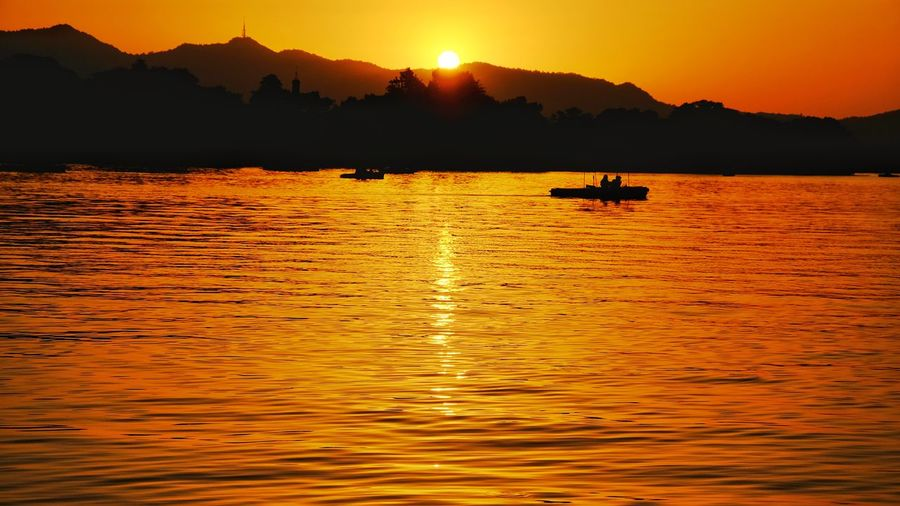 Sunset Mountain Reflection Water Orange Color Lake Silhouette Nature Mountain Range Outdoors Landscape Scenics Fisherman Yellow Reflection Tranquility China View FUJIFILM X-T10 Light And Shadow West Lake, Hangzhou Lake View Hangzhou,China Vacations Warm Glow Travel