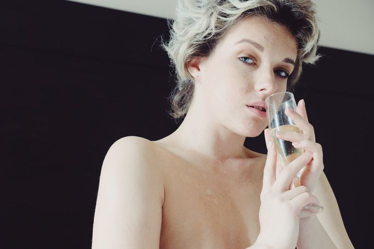 Portrait of topless woman drinking champagne at home