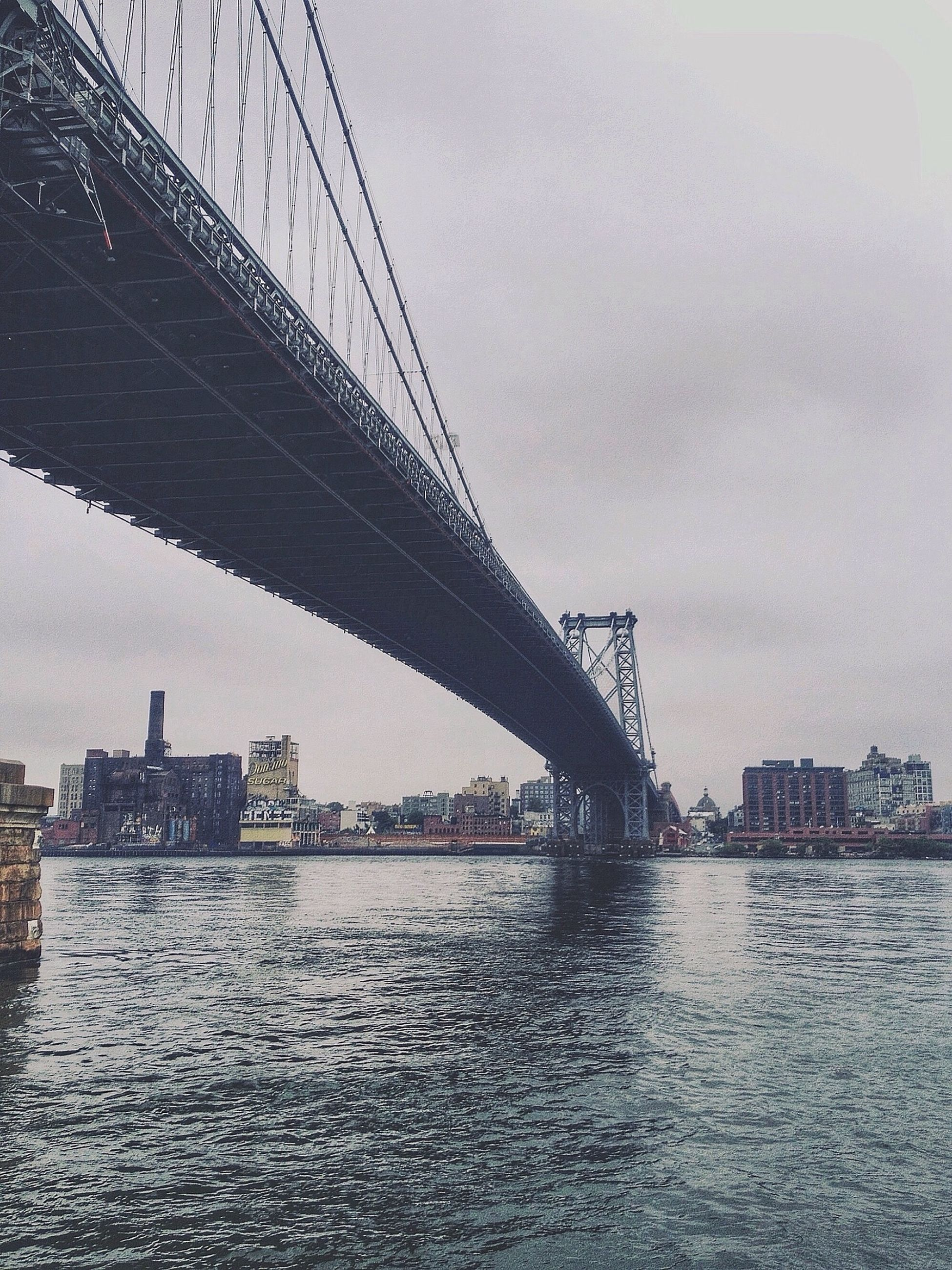 architecture, built structure, connection, bridge - man made structure, water, sky, river, waterfront, engineering, suspension bridge, city, bridge, transportation, building exterior, sea, low angle view, cloud - sky, outdoors, rippled, travel destinations