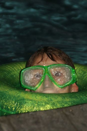 Close-up portrait of teenage boy wearing swimming goggles in pool