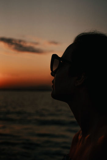 Portrait of woman wearing sunglasses against sea during sunset