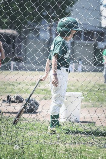 Full length of boy standing on chainlink fence