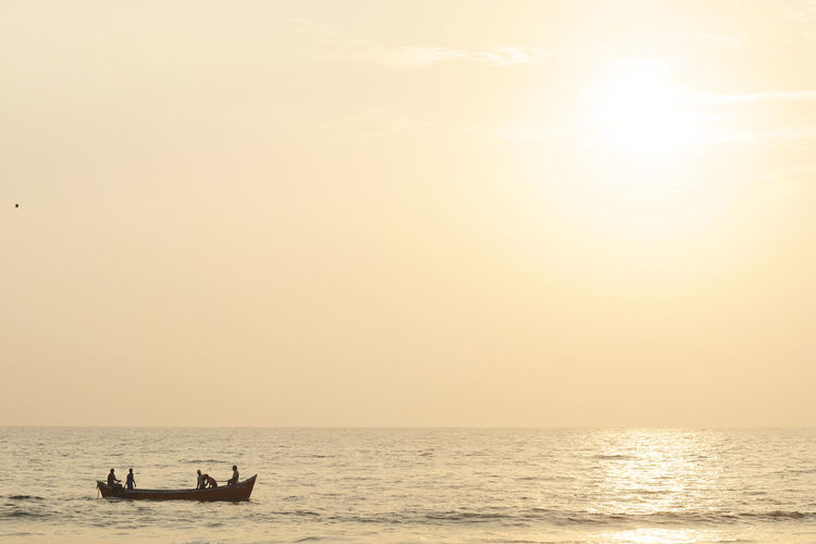 Boat in sea against clear sky during sunset