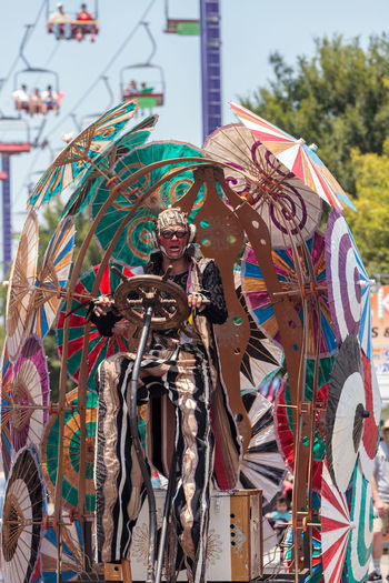 Costa Mesa, CA, USA - July 14, 2017: Theatrical circus performer Derrick Gilday, part Mango and Dango, performs with Dragon Knights steampunk stilt walkers at the Orange County Fair in Costa Mesa, CA on July 16, 2016. Editorial use only. Bicycle Circus Costa Mesa Derrick Gilday Dragon Knights Entertainer Fair Fun Mango And Dango OC Fair Orange County Fair Performance Performer  Steampunk Stilt Walkers Umbrella