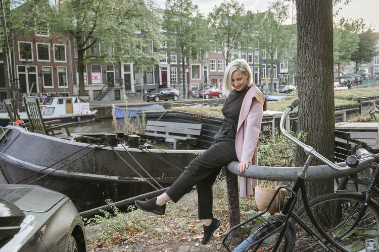 Portrait of smiling woman sitting on bicycle against trees
