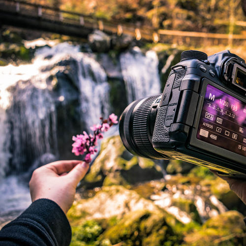 Close-up of hand holding camera against blurred waterfall and bridge in background