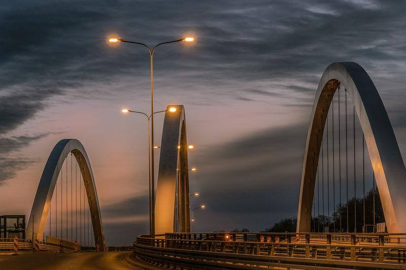 Ferris wheel by bridge against sky at dusk