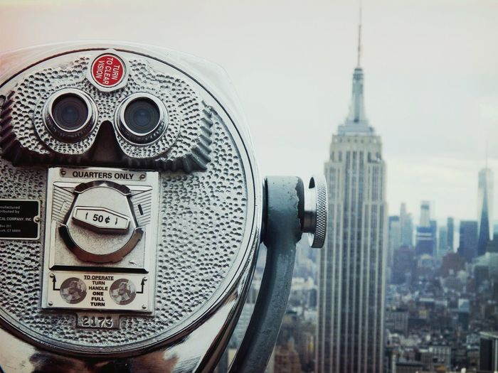 Close-up of coin-operated binoculars at observation point against cityscape