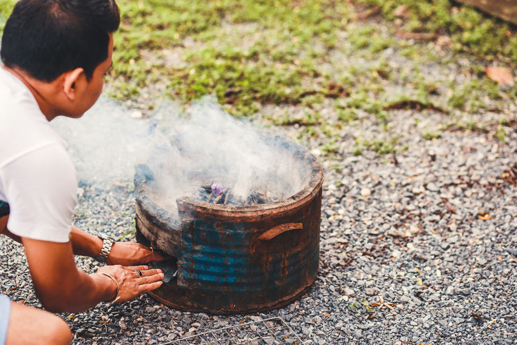 Cropped image of man burning fire in fire pit