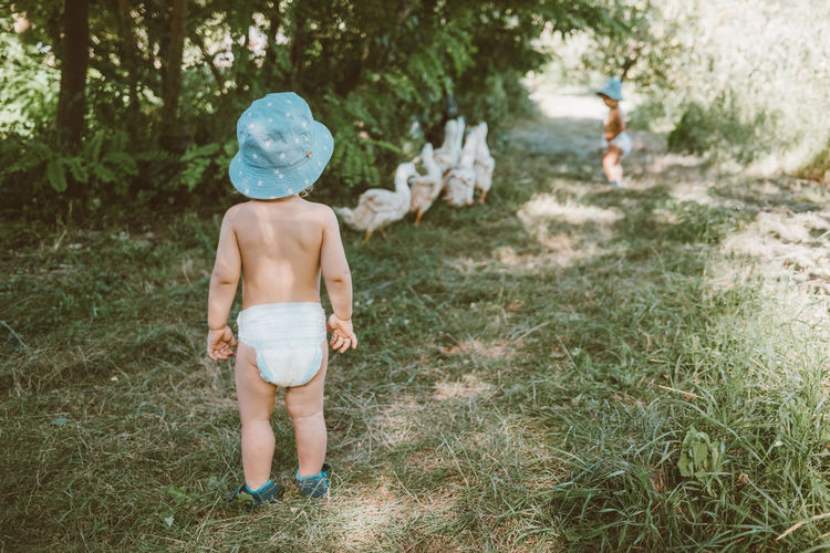 Rear view of shirtless boy standing on grassland
