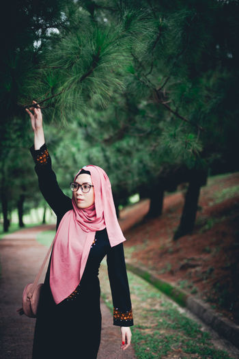 Woman touching branch while standing in park