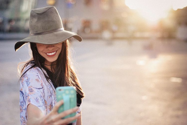 Happy woman taking selfie from mobile phone on street in city during sunset