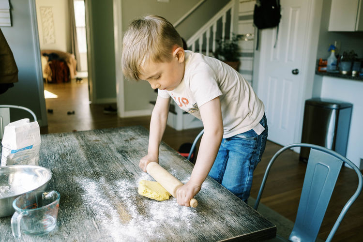 Boy standing on table at home
