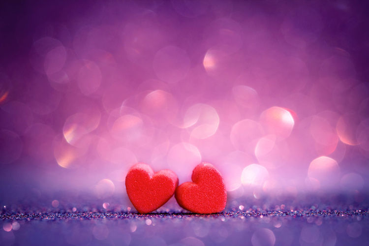 Close-up of heart shape decorations on table against purple background