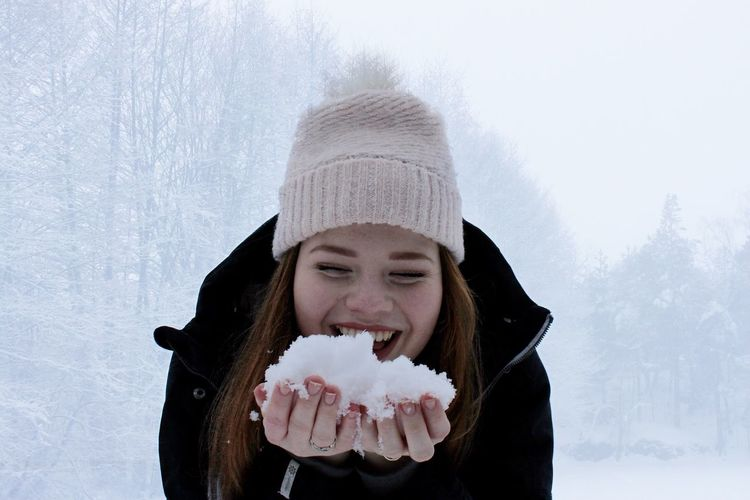 Portrait of a young woman holding snow
