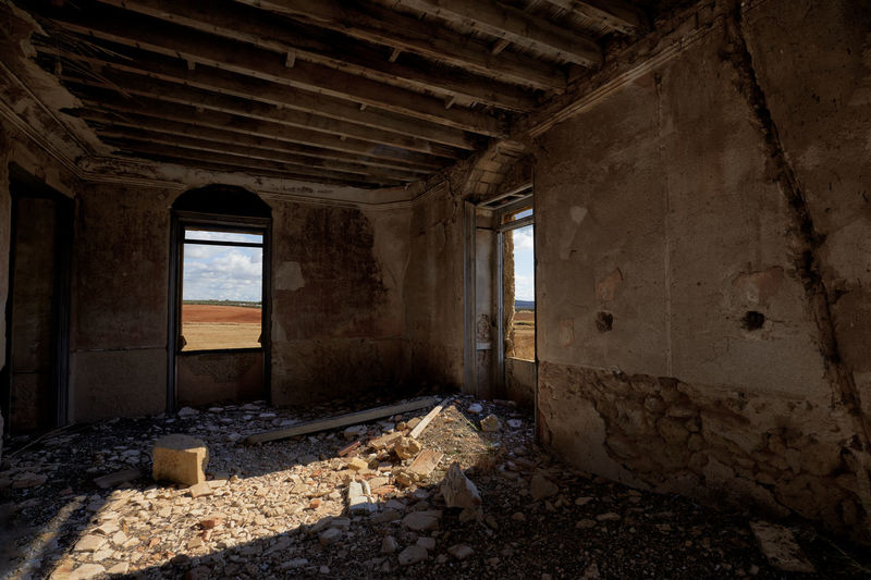Old room with debris, broken windows and fissured wall