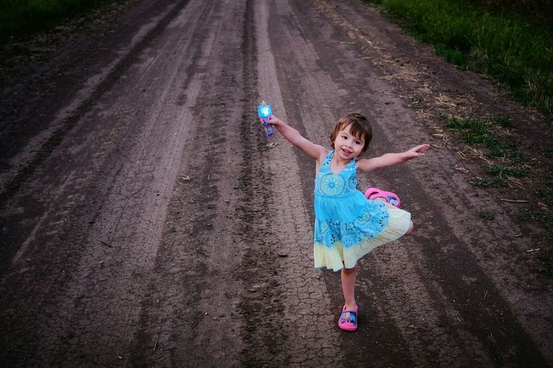 She has her own special little dance she does when she waves her magic wand. Magic Moments Dirt Road A Day In The Life Candid Portrait Color Photography Flash Photography A Day In The Life Gesture Devineliving Outsiderin Childhood Empty Places