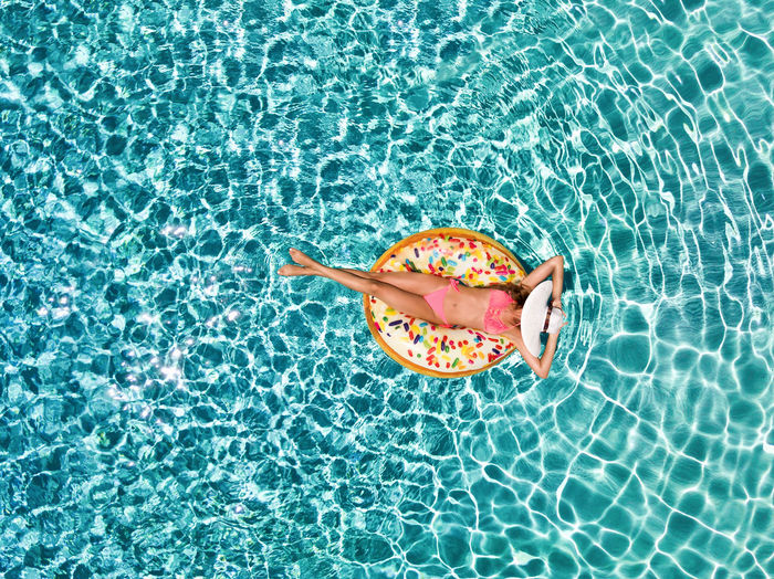 Directly Above Shot Of Woman Relaxing On Inflatable Ring In Swimming Pool