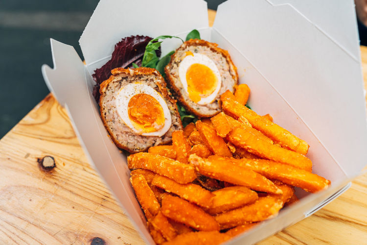 Close-up of scotch eggs with french fries in box on table