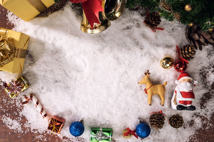 Close-Up Of Christmas Decorations With Fake Snow On Table