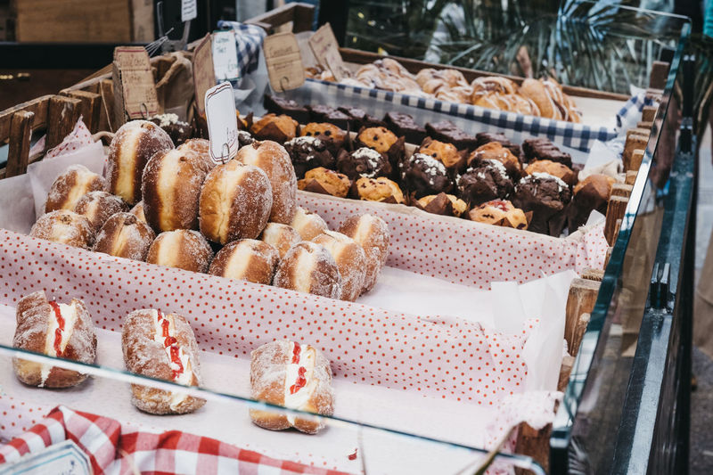 Variety of fresh doughnuts, muffins and pastries on sale at a food market in london, uk.