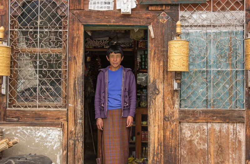 Smiling woman Travel Photography Street Photography Bhutan ASIA Himalayas Architecture Front View Standing One Person Built Structure Adult Real People Three Quarter Length Lifestyles Portrait Building Exterior Looking At Camera Senior Adult Day Building Entrance Door Outdoors Casual Clothing