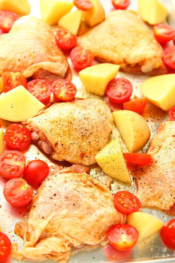 Chicken sheet pan dinner ready to cook Home Cooking Homemade Food Natural Light Textures Balanced Meal Cherry Tomatoes Chicken Thighs Close-up Colorful Delicious Food Freshness Healthy Eating No People One Pan Meal Overhead Potatoes Raw Food Seasoned Sheet Pan Dinner Studio Shot Uncooked Vegetables Vertical