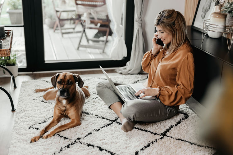 Businesswoman talking on phone while using laptop at home