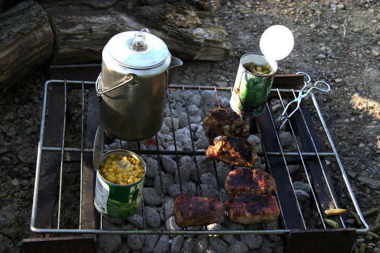 High Angle View Of Meat And Cans On Barbecue Grill