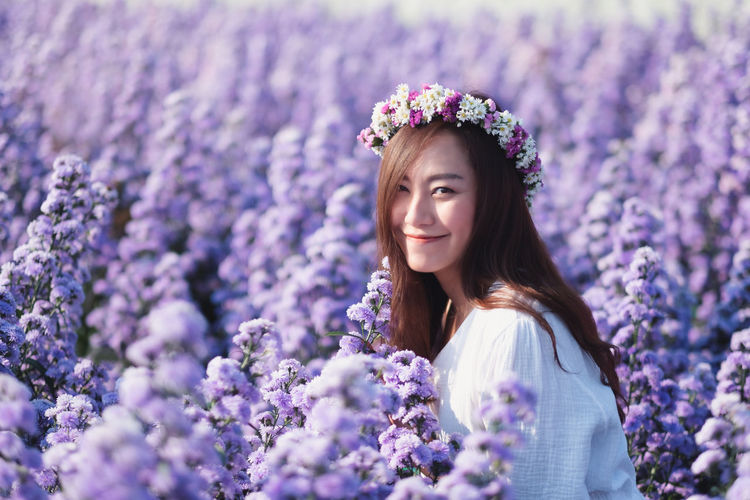 Portrait of smiling woman standing against purple flowering plants