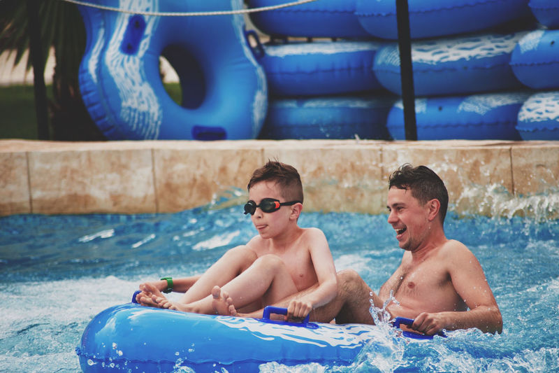 Happy father with son siting on inflatable raft in pool